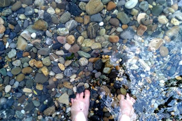Feet in Lake Geneva on the pebbles in Geneva, Switzerland.